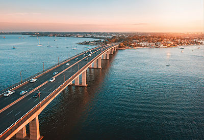 Cars and traffic trvelling across Georges River on the Captain  Cook Bridge Sans Souci as the sun sets in the west. NSW Austr...