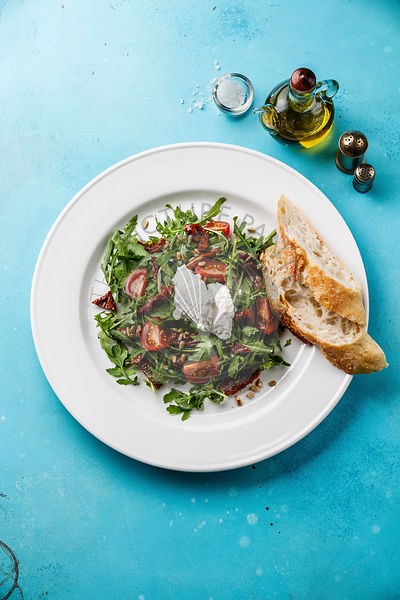 Salad with arugula, sun-dried tomatoes, sunflower seeds, ricotta cheese and bread on white plate on blue background