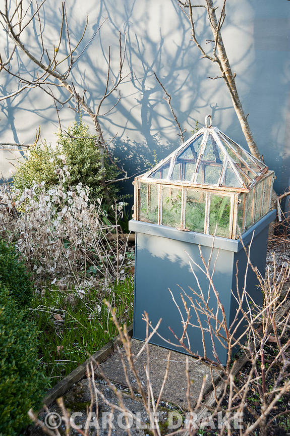 A cast iron Victorian lantern cloche set on a pedestal in a formal kitchen garden surrounded by fruit bushes casting shadows ...