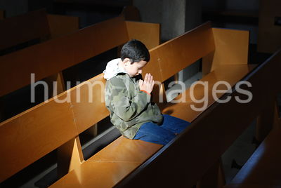 Young boy praying while sitting on a church pew