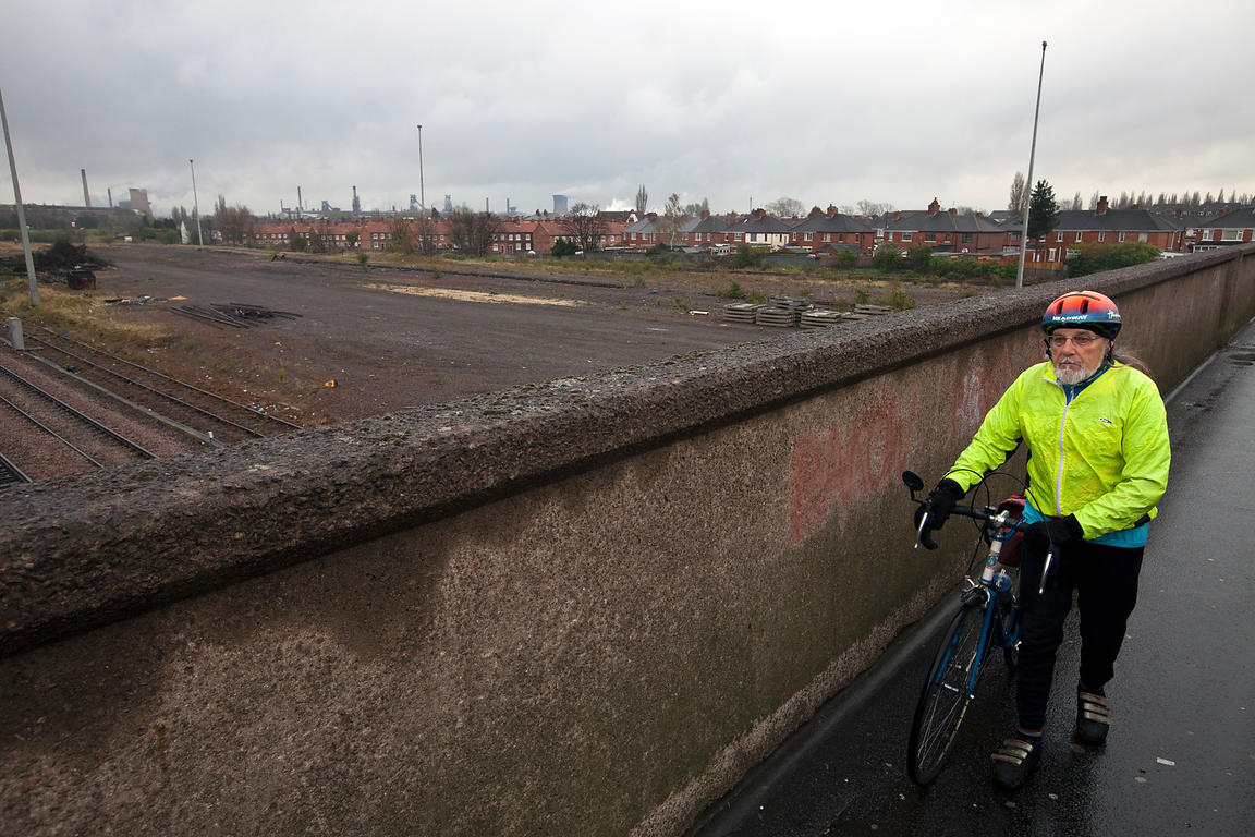 UK - Scunthorpe - John Shipley, 73 a keen cycling enthusiast, walks across a bridge near the steelworks