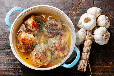Roast chicken stew in casserole and garlic on wooden background