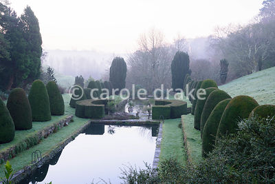 Clipped yews llne the Canal garden with swimming and lily ponds in the garden at Mapperton, Dorset in winter