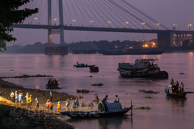 Nighttime view of Lakshmi idols being immersed in the Hooghly Rver - and then immediately taken out to avoid pollution - duri...