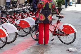 A woman at the bike sharing station, 'bicing' in Barcelona, Spain
