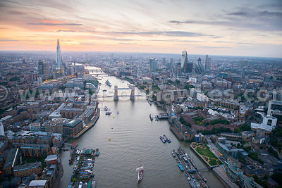 A dusk aerial view looking up the River Thames showing St Katherines Dock on the right of the image, Tower Bridge, The City o...
