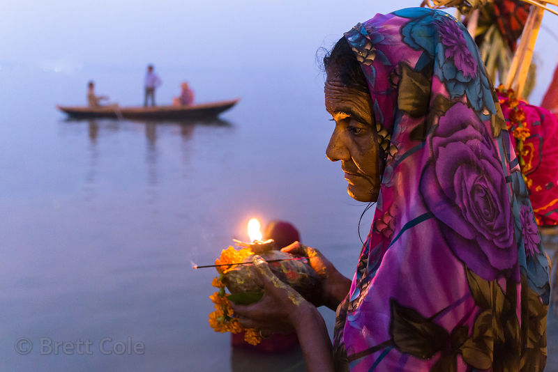 A woman prays at sunset along the Ganges River during Chhath Puja, Varanasi, India. Chhath Puja is a devotion to the Sun God Surya in which people gather at sunset and then on the following sunrise and offer prayers.