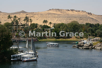 Tourist boats on the River Nile at Aswan, Egypt, with the desert immediately beyond the west bank