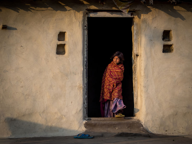 This photograph of a kid looking out curiously from her house was shot in a small village in Jojawar