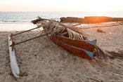 Fishing boat lying on the Grand Pavois beach at sunset, Mahajanga, Madagascar