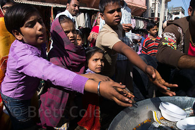 People receive a free meal during a charitable community cooking day in Pushkar, Rajasthan, India