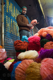 A man sells colorful yarns at a market in Varanasi, India.