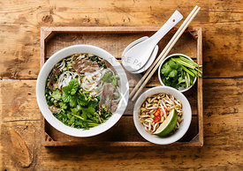 Pho Bo vietnamese Soup with beef in wooden tray on wooden background