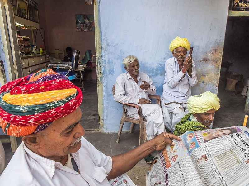 A group of rural men gather in the veranda of a shop. This photograph was shot in Jojawar