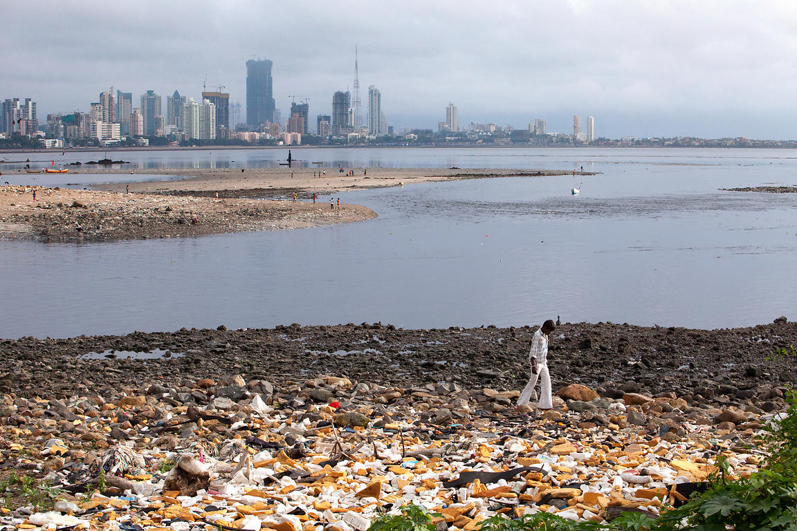 Men walk through garbage on the banks of Mahim Bay (Arabian Sea), Mumbai, India.