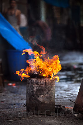 A fire burns in a street in the Dharavi slum of Mumbai, India.