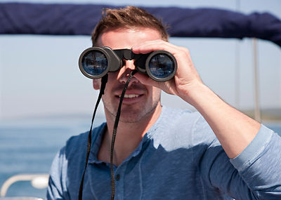 Man with binoculars on yacht