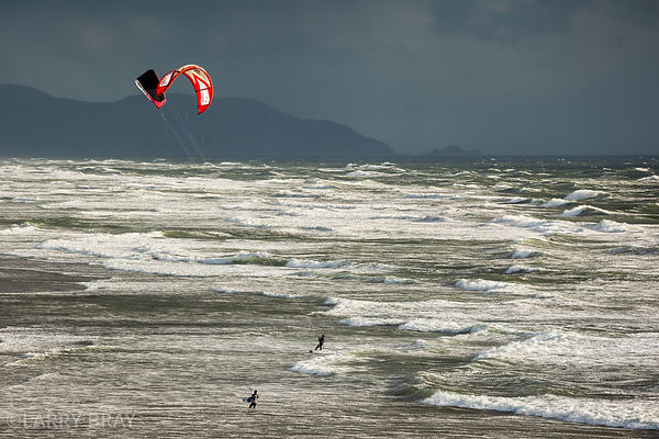 Kite surfers with stormy skies at Ocean Beach, San Francisco, USA
