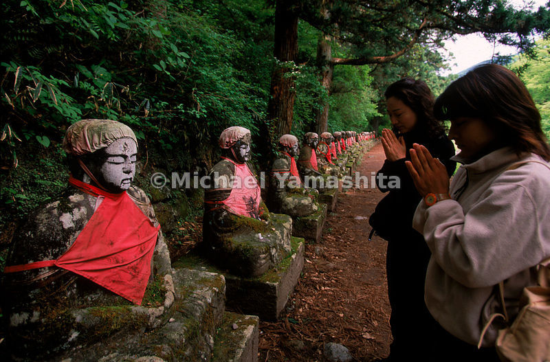 Passersby stop to say a prayer before a row of statues of jizo, a protector of children and travelers.