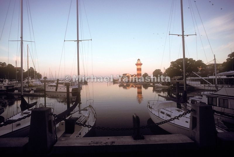 A view of the lighthouse and boats on Hilton Head Island at sunset.