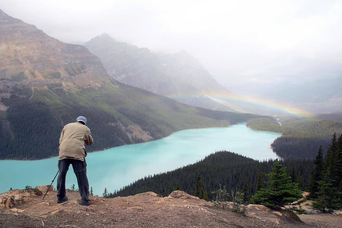 A photographer takes a photo of a rainbow over Peyto lake. Banff NP, Canadian Rockies.