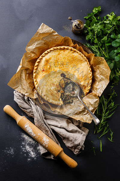 Meat Pie with herbs on blackboard slate background