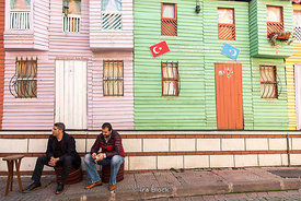 Men sitting on a street against a colorful wall in Istanbul.