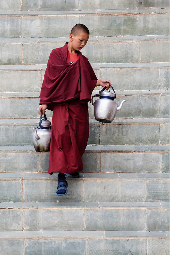 Novice Monk Carrying Kettles of Butter Tea