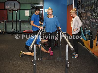Physical Therapists Assisting Young Female With A Disability