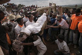 "People carry a body wrapped in a sheet as they take part in a funerary tradition called the Famadihana in the village of Ambohijafy, a few kilometres from Antananarivo, on September 23, 2017. During the Famadihana, which can be translated as ""turning of the bones"", several crypts are opened and people take the bodies of their ancestors from the family crypts and rewrap them in fresh cloth, then dance with the corpses in their arms at the pace of traditional Malagasy band's music. The Famadihana is a pillar in the Malagasy ancestor's worship and is celebrated each three, five or seven years."