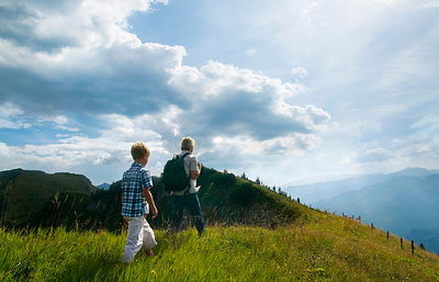 Father and son hiking on grassy hilltop
