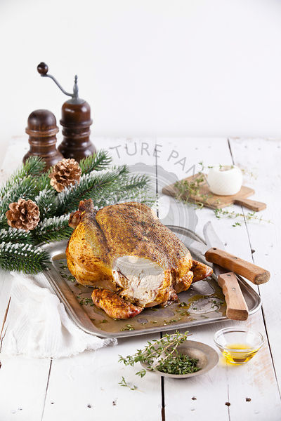 Whole roasted chicken on white wooden background