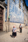 An elderly woman and man walk past the Capela Das Almas in Porto, Portugal