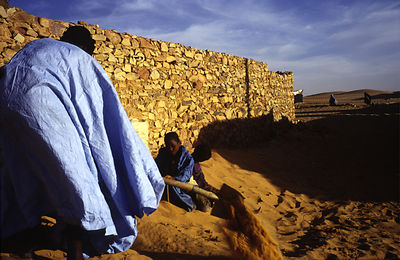 Mauritania - Chinguetti - A man digs himself out of his house in the morning after the wind has blown sand and covered his do...