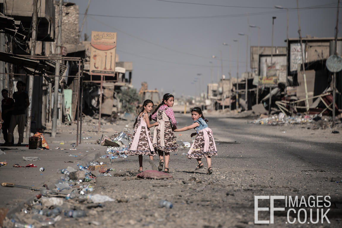 Girls in dresses made from old Soldiers uniforms and pink offcuts walk home in a recently liberated area of West Mosul. July ...