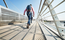 GATESHEAD, ENGLAND, UK - MAY 08, 2018: Pedestrians and commuters crossing the Gateshead Millennium Bridge