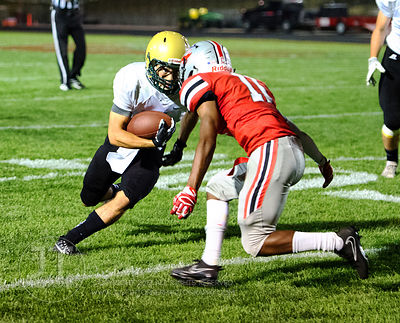 Iowa City West's Andre White (1) runs downfield into the defending Iowa City High's Marquel Poole (11) during the first half ...