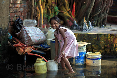 A girl colletcts water from a communal spigot while wading through monsoon floods, Salkia, Howrah, India