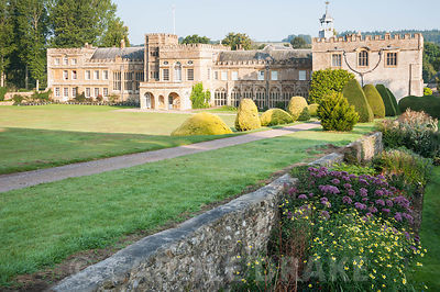 House viewed from the rock garden, across the south lawn with its clipped yews. Forde Abbey, nr Chard, Dorset, UK