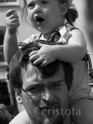 a child rides on her father's shoulders on Mazey Day, Penzance Golowan Festival