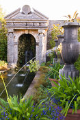 Rill pool flanked by turned oak urns spouting water through gilded lions' heads, with golden agaves in their tops. Planting i...