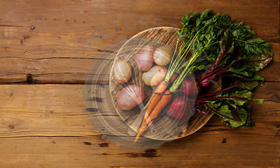 Fresh vegetables carrots, potato and beets on round cutting board on wooden background copy space