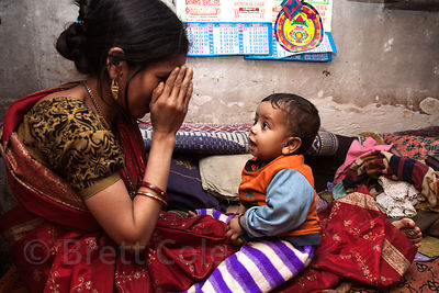 A mother plays peek-a-boo with her baby at their house in Howrah, India