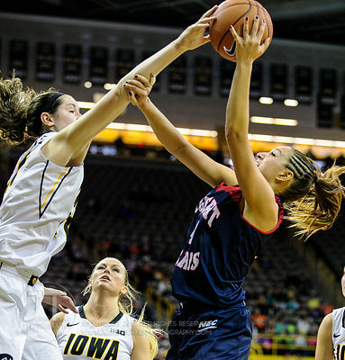 Robert Morris' Ashley Ravelli (14) has her shot blocked by Iowa's Bethany Doolittle (51) during the first half of play at Car...