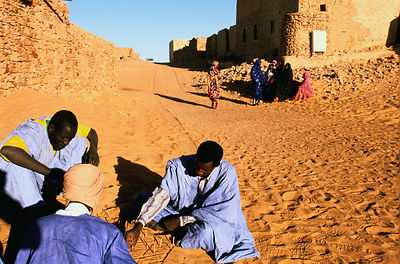 Men play a traditional game in the sand
