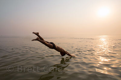 A man dives into the Ganges River, Tulsi Ghat, Varanasi, India