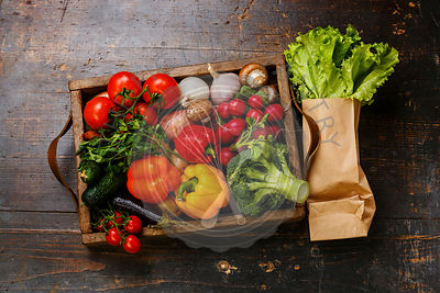 Fresh vegetables in wooden box and lettuce on wooden background