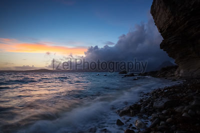 The sun sets over a cloudy Cuillin ridge as the waves lap the shores of Elgol Bay on the Isle of Skye.
