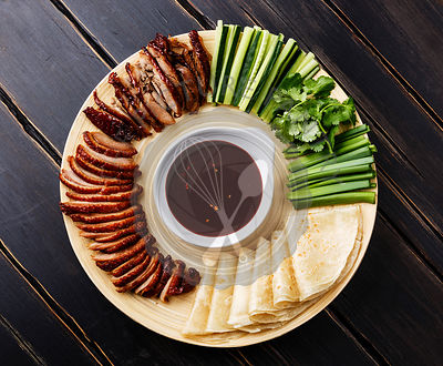 Sliced Peking Duck served with fresh cucumber, green onions, cilantro and roasted wheaten chinese pancakes with Hoysin sauce ...