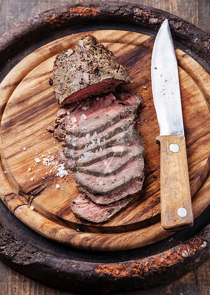 Roast beef on cutting board and knife